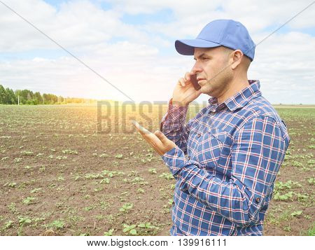 Farmer In A Plaid Shirt Controlled His Field.talking On Phone.