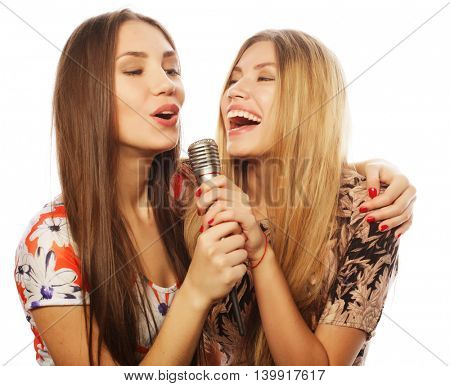 two beauty girls with a microphone singing and having fun