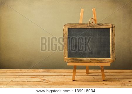 Chalkboard on wooden easel on wooden table over grunge background