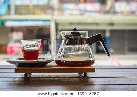 drip coffee cup and coffee pot on wood table in coffee shop. side view