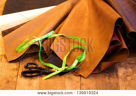 Natural sample leathers with measuring tape and scissors on a wooden table background