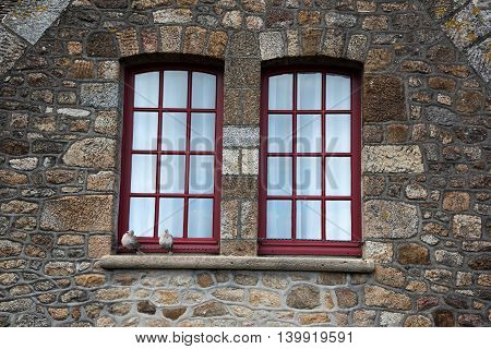 Two pigeons sit on old windows of weathered stoned building