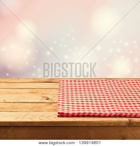 Christmas festive bokeh background with empty wooden table and red checked tablecloth