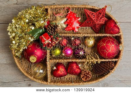 Christmas decoration in wicker box over wooden background