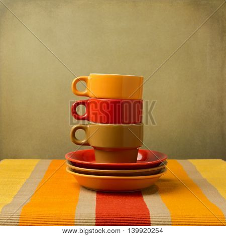 Stack of colorful coffee cups on tableccloth or place mat