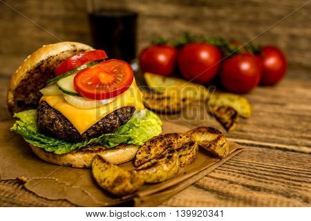 Grilled beef hamburber with vegetables on wood table