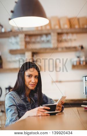 Portrait of young woman holding mobile phone and coffee cup in office cafeteria