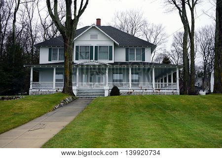 WEQUENTONSING, MICHIGAN / UNITED STATES - DECEMBER 23, 2015: A white mansion with a long walkway on Beach Drive in Wequetonsing.