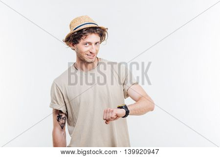 Portrait of a smiling man looking on wrist watch over white background