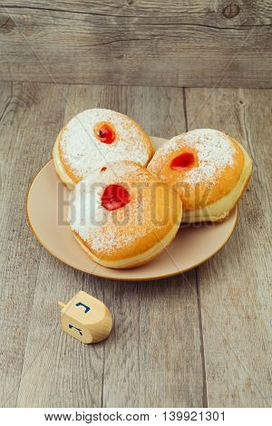 Donut for jewish holiday hanukkah on plate and dreidel on wooden background