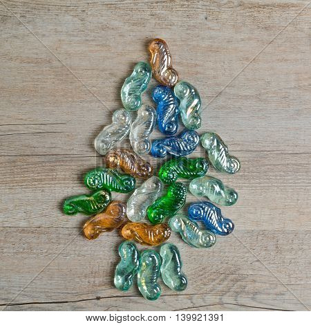 Christmas tree symbol made from stones on wooden background