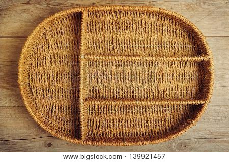 Empty wicker tray box over wooden background