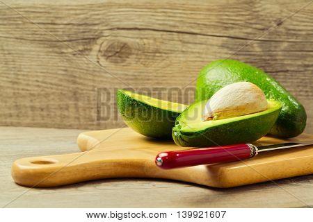 Avocado cut in half over wooden background
