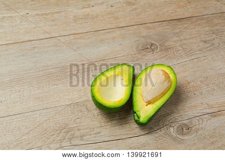 Sliced green avocado over wooden table background