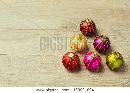 Christmas tree made from decoration balls over wooden background