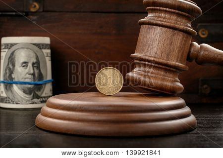 Judge Hammer closeup with twenty eurocent and rolled bundle of dollars on a wooden background. Concept of corruption bribery or auction bidding