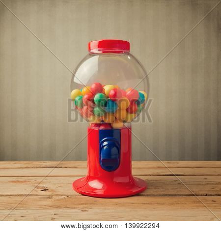 Gumball machine on wooden table over retro wallpaper