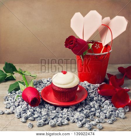 Valentine's day cupcake and roses on wooden table