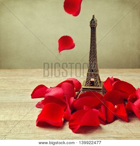 Small Eiffel tower with roses petals on wooden table