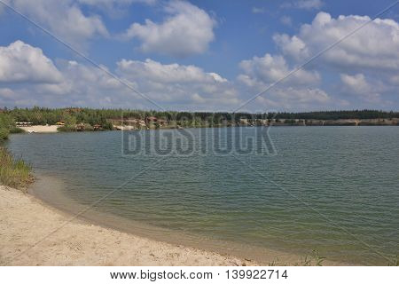 Deserted sand beach of a small lake. Summer sunny day with clouds