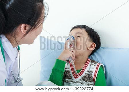 Sad child having respiratory illness helped by health professional with inhaler. Pediatrician take care asian boy with asthma problems making inhalation with mask on his face at hospital.