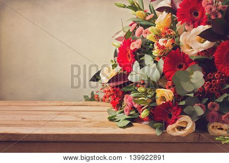 Flower bouquet on wooden table over grunge background