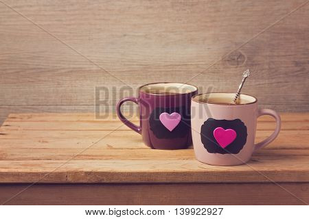 Couple of tea cups with chalkboard stickers and hearts on wooden table