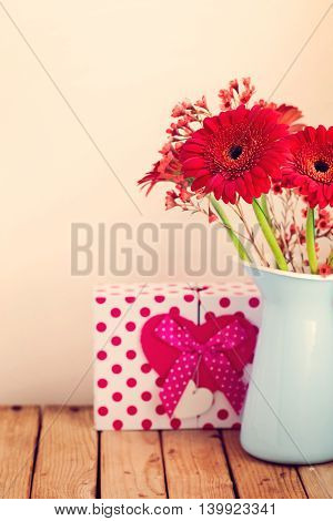 Gerbera daisy flower bouquet with gift box over retro background