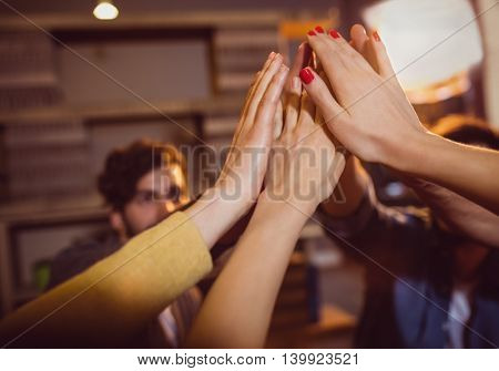 Close-up of colleagues giving high five during meeting at office