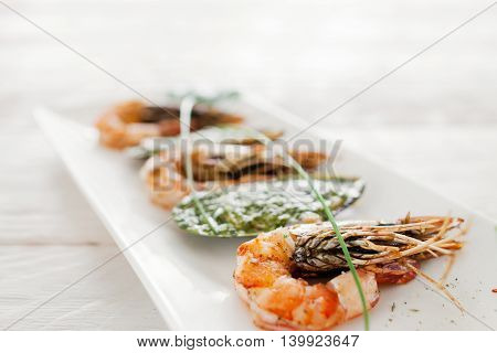 Grilled shrimp and stuffed mussel on white, close-up. Prepared mediterranean meal of fresh seafood