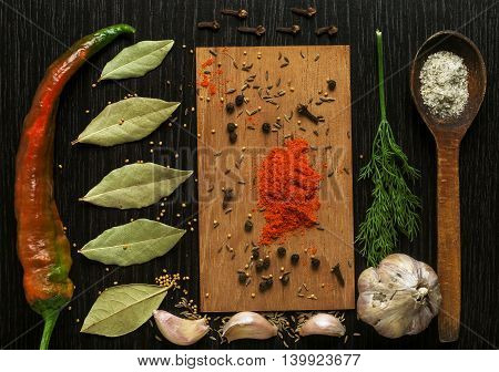 A set of spiced and herbs on a black wooden board