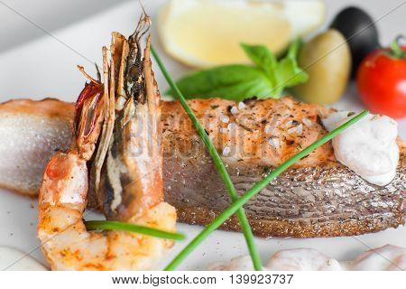 Close-up of grilled shrimp and salmon, seafood culinary. Delicious mediterranean meal, restaurant serving