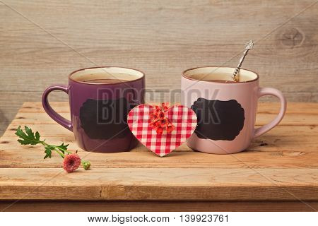Couple of tea cups with chalkboard stickers and heart shape on wooden table