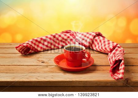 Coffee cup with checked tablecloth on wooden table over bokeh background