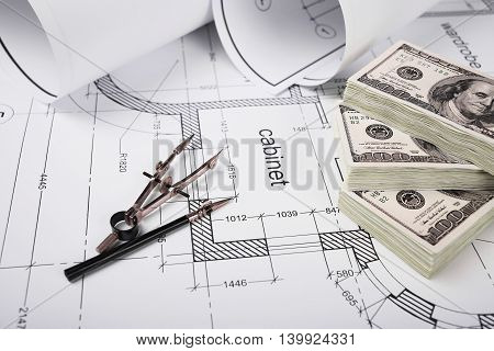 Construction drawings, drawing instruments, financing of the construction, packs of dollars, building drawing on paper, a set of drawing tools, blueprints rolled up into a roll.