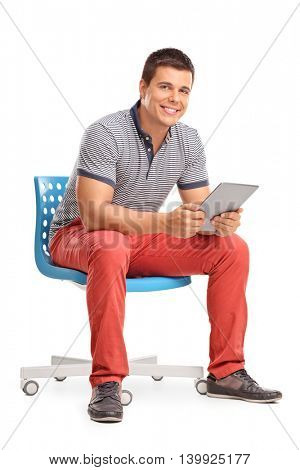 Vertical shot of a young man holding a tablet and sitting on a chair isolated on white background
