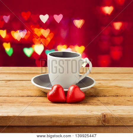 Coffee cup with heart shape chocolate over bokeh background