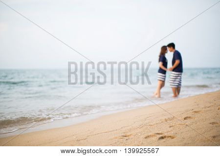 The short focus of sand beach and the couple in the background out of focus