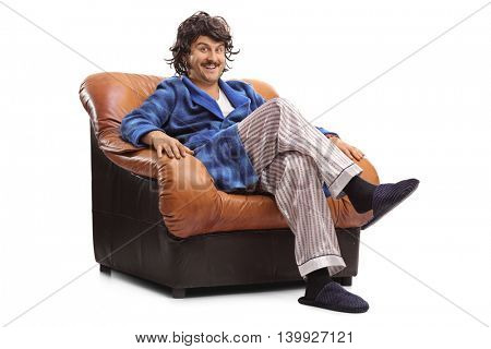Joyful guy with retro hairstyle sitting on a brown leather armchair isolated on white background