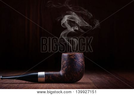 Smoking pipe on a wooden table