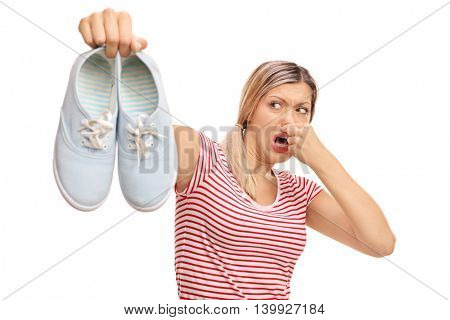 Disgusted woman holding a pair of stinky shoes isolated on white background