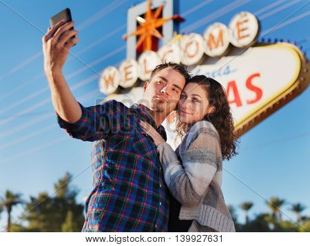 couple in front of las vegas sign taking selfie with smartphone