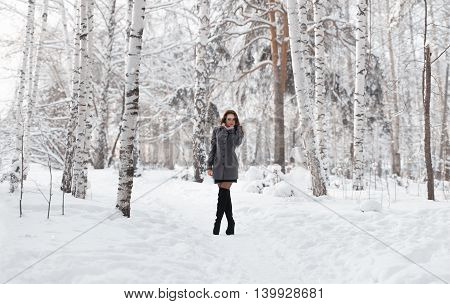 Beautiful young girl in a white winter forest