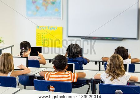 Rear view of children using digital tablets in classroom