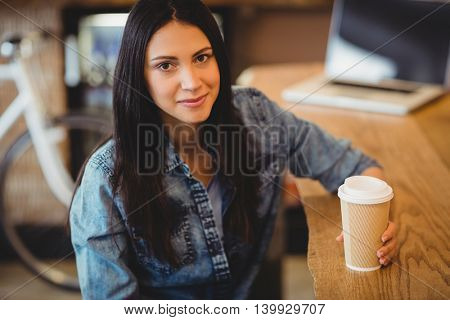 Portrait of beautiful young woman having coffee at office cafeteria
