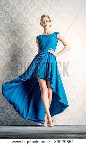 Fashion portrait of a beautiful young woman in  elegant evening dress posing in motion by a vintage wall. Hairstyle.