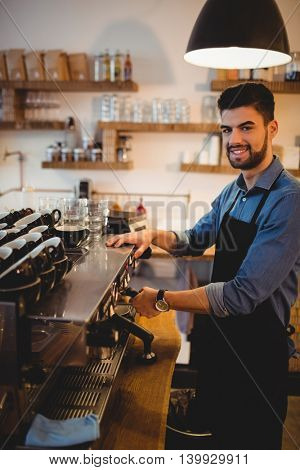 Portrait of young man taking coffee from espresso machine at office cafeteria