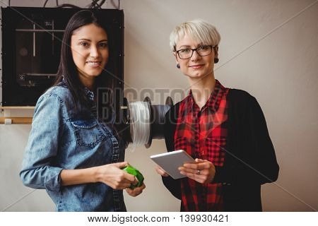 Portrait of female graphic designers holding digital tablet at office