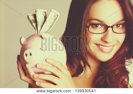 Smiling girl holding piggy bank money