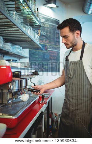 Young male waiter using espresso maker at coffee house